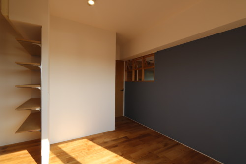 アクセント壁と室内窓のある寝室